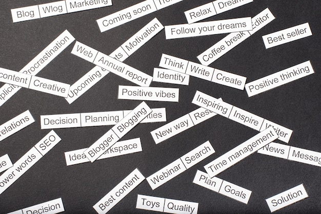 Nuage de mots de thèmes commerciaux découpés dans du papier sur un fond gris