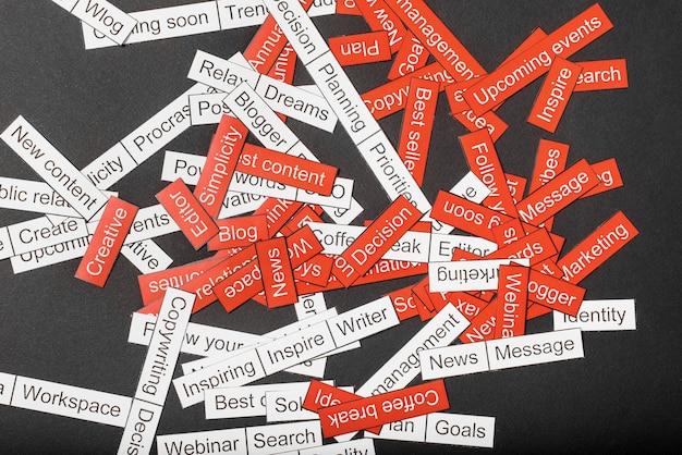 Nuage de mots de thèmes commerciaux découpés dans du papier rouge et blanc sur une surface grise