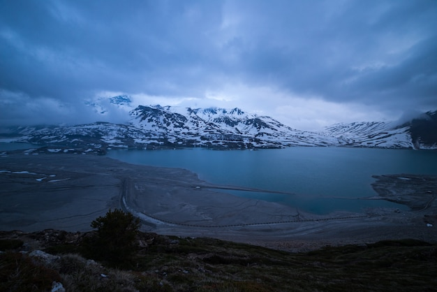 Nuages au crépuscule heure bleue, lac et montagne enneigée, hiver froid, paysage de fjord nord