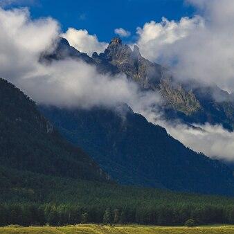 Nuages au-dessus des montagnes rocheuses envahies par les arbres. photographié dans le caucase, en russie.