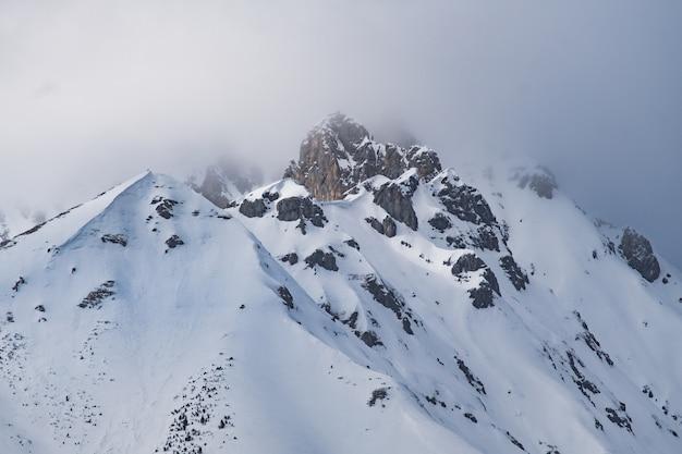 Nuages au sommet d'une montagne enneigée dans les alpes autrichiennes