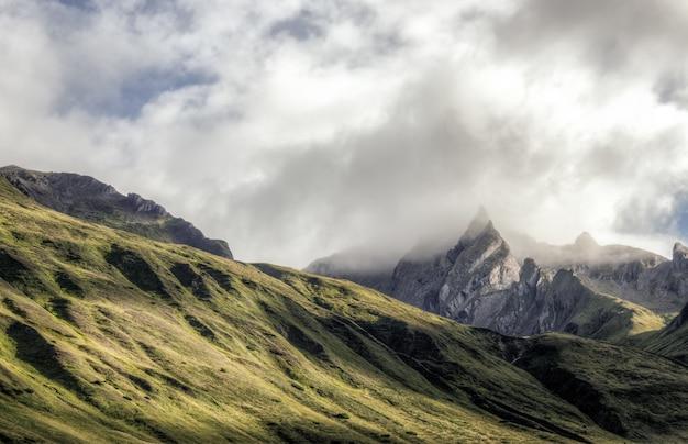 Nuages blancs au sommet de la montagne verte