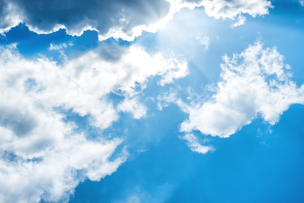 Nuages blancs duveteux sur le ciel bleu avec des rayons de soleil. fond de nature