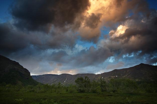 Nuages dans le ciel au-dessus des montagnes éclairées par le soleil au coucher du soleil.