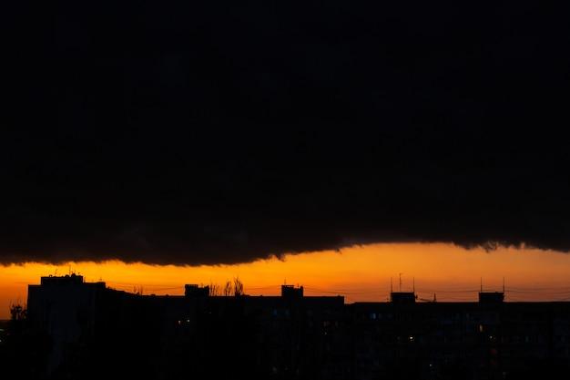 Nuages noirs au coucher du soleil. coucher de soleil orange vif et nuages sombres. ciel d'orage