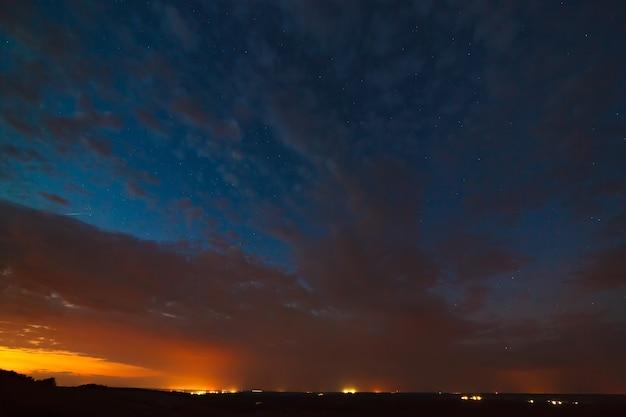 Nuages de nuit sur fond d'étoiles brillantes dans le ciel après le coucher du soleil