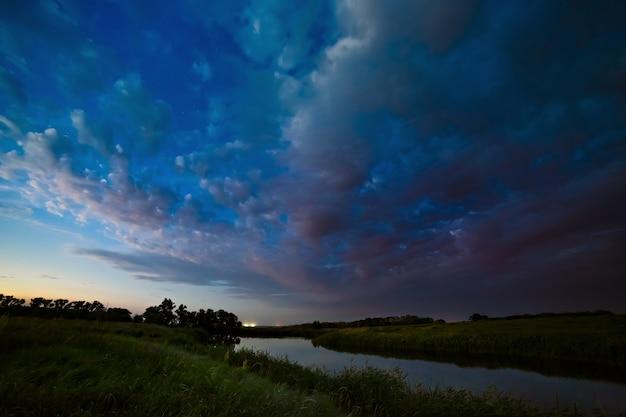 Nuages d'orage dans le ciel après le coucher du soleil sur la rivière