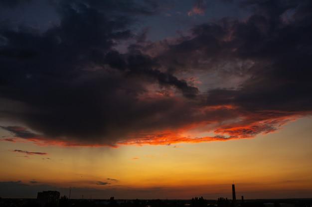 Nuages d'orage noirs au coucher du soleil. coucher de soleil orange vif et nuages sombres. ciel d'orage