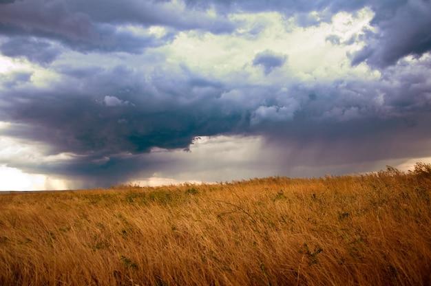 Nuages de pluie, rayons de soleil, crépuscule, ciel orageux et prairie d'automne