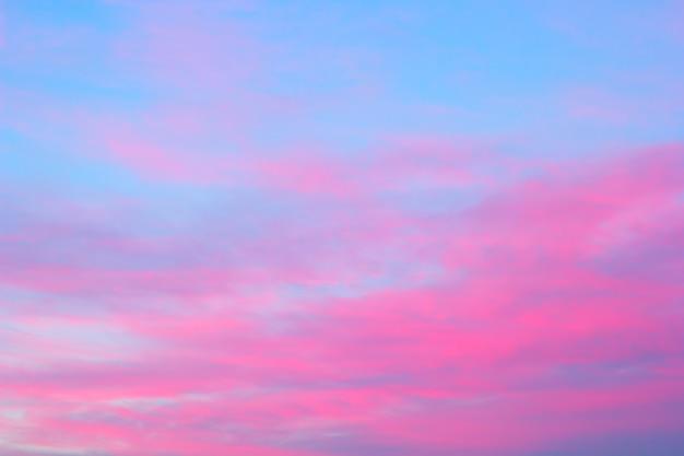 Nuages roses vifs sur un ciel bleu au coucher de soleil
