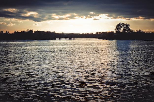 Nuages sombres au coucher du soleil, lever de soleil au-dessus de la surface de l'eau, filtre