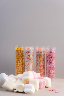 Nuages de sucre blancs et roses sur fond gris et avec des pots d'ingrédients de sucre
