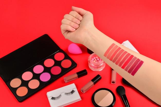 Nuancier de rouge à lèvres sur la main de la femme. produits de maquillage professionnels avec produits de beauté cosmétiques, fond de teint, rouge à lèvres, ombres à paupières, cils, pinceaux et outils.