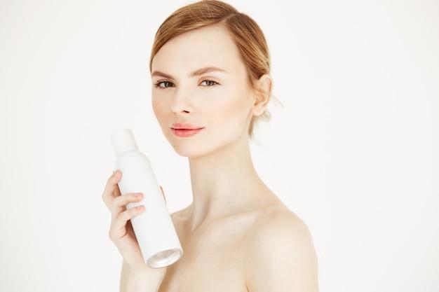 Nue belle fille blonde avec une peau parfaite fraîche souriant tenant un flacon pulvérisateur de cosmétologie.