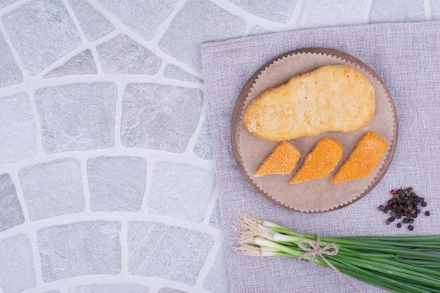 Nuggets sur une planche de bois avec un tas d'oignons verts