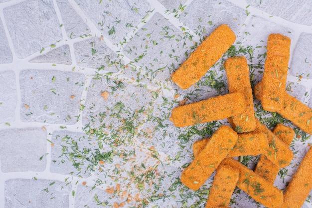Nuggets de poulet aux herbes et épices sur fond gris.