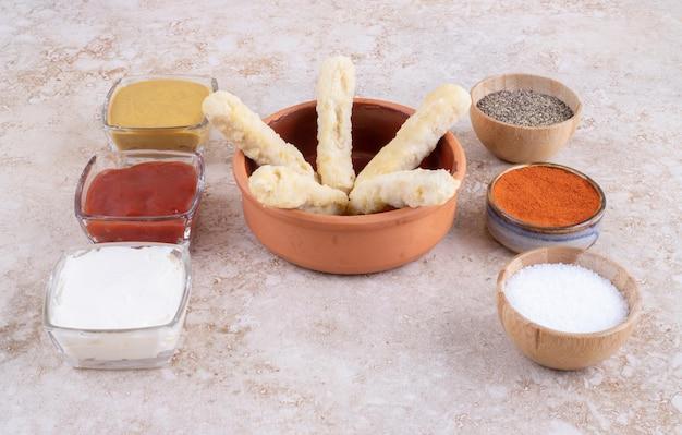 Nuggets de poulet et bâtonnets de fromage sur une planche en bois avec une variété de sauces autour.