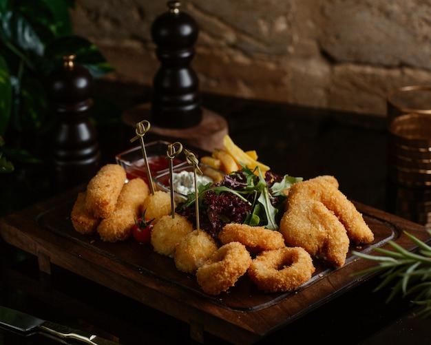 Nuggets de poulet avec des bâtonnets d'oignon, fast food avec salade verte