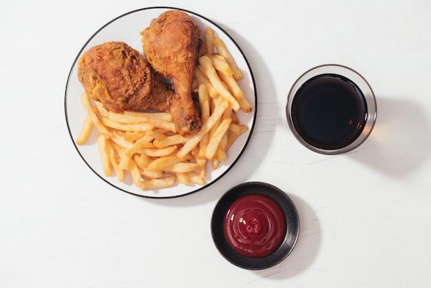 Nuggets de poulet croustillants panés frits avec frites sur plaque de bois, ketchup et boisson gazeuse à côté