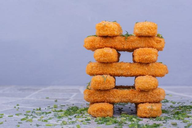 Nuggets de poulet frit avec garniture croustillante sur fond bleu.