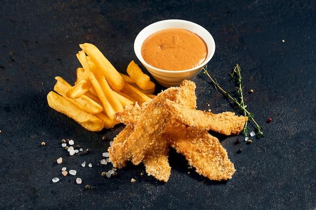 Nuggets de poulet avec frites et sauce sur fond sombre.