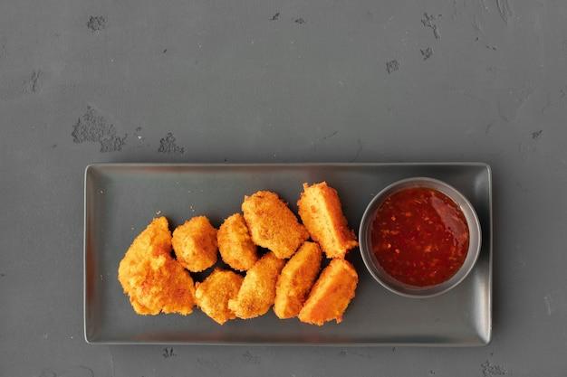 Nuggets de poulet frits servis avec sauce chili sur fond gris