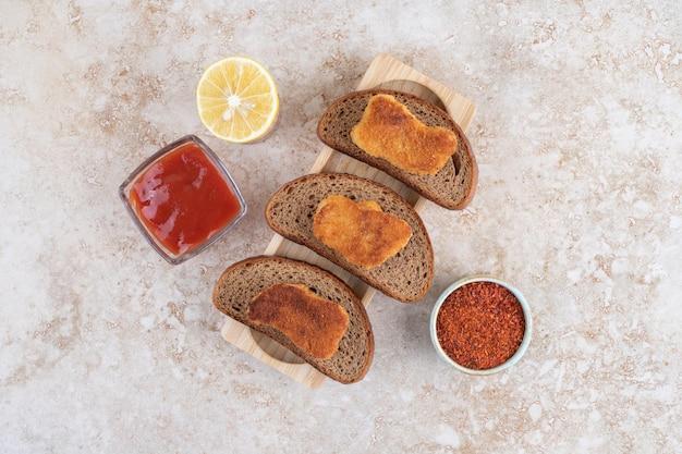 Nuggets de poulet frits sur des tranches de pain noir servis avec des sauces.