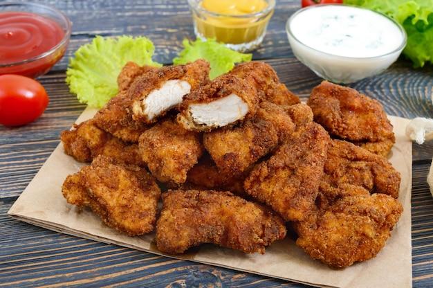 Nuggets de poulet. morceaux de viande croustillante frite, sur papier avec différentes sauces sur une table en bois. collation traditionnelle.