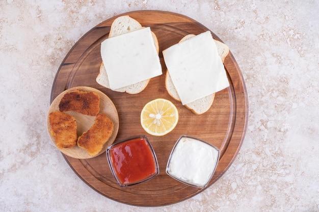 Nuggets de poulet sur une planche de bois avec sauces de côté.