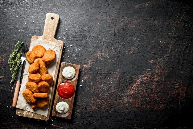 Nuggets de poulet sur une planche à découper avec du thym et des sauces. sur table rustique sombre