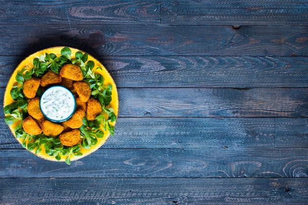 Nuggets de poulet à la sauce au yaourt sur un fond en bois