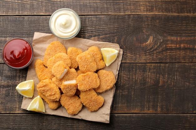 Nuggets de poulet à la sauce rouge et blanche sur fond de bois marron. vue de dessus avec un espace pour le texte