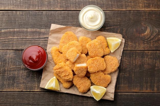 Nuggets de poulet à la sauce rouge et blanche sur fond de bois marron. vue d'en-haut