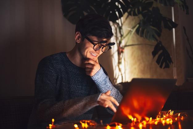 Nuit jeune homme heureux portant des lunettes rondes, à la recherche d'un ordinateur portable dans une pièce sombre avec des guirlandes à la maison.
