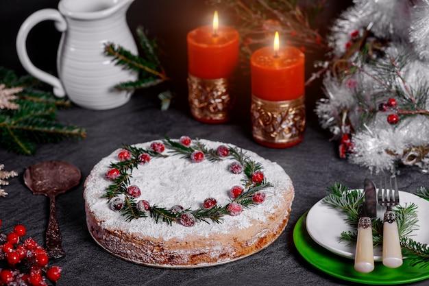 Nuit de noël avec gâteau festif décoré de branches de canneberge et de pin