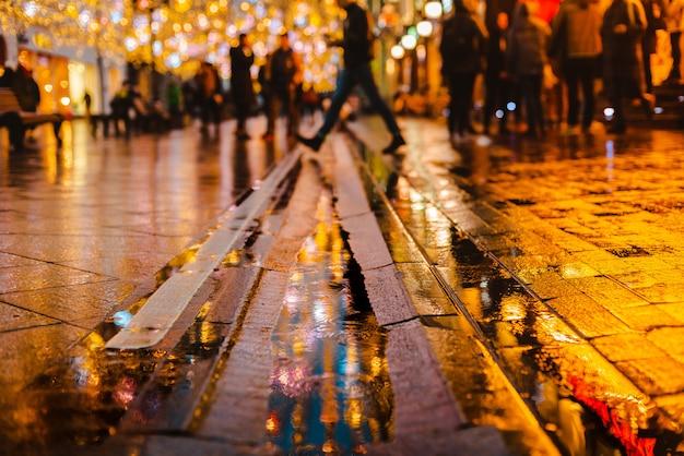 Nuit pluvieuse dans une grande ville, reflets de lumières sur la chaussée mouillée.