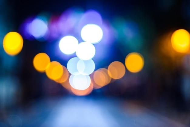 Nuit urbaine défocalisée avec des cercles colorés.