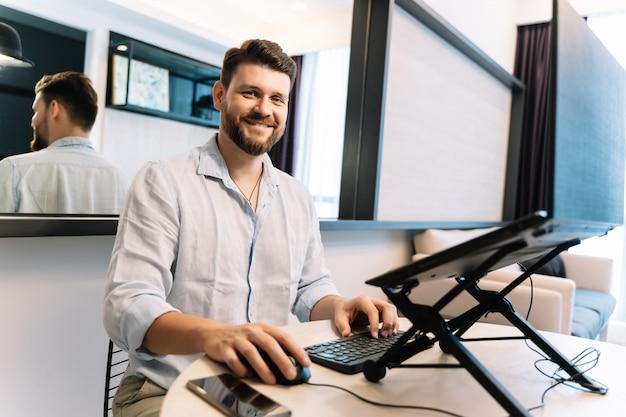 Numérique travaillant à distance avec un ordinateur portable tout en souriant