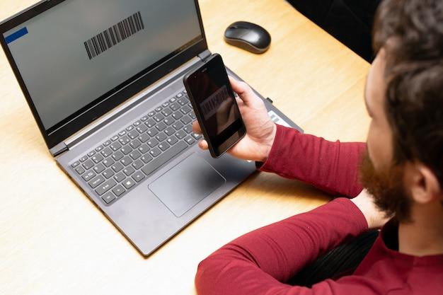 Numérisation de personne avec téléphone portable, code à barres sur un écran d'ordinateur, paiement moderne en ligne avec smartphone d'application de numérisation