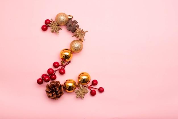 Numéro 2 fait avec des ornements de noël sur fond rose