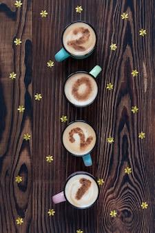 Numéro 2021 dans quatre tasses à café sur une table en bois marron avec des étoiles d'or