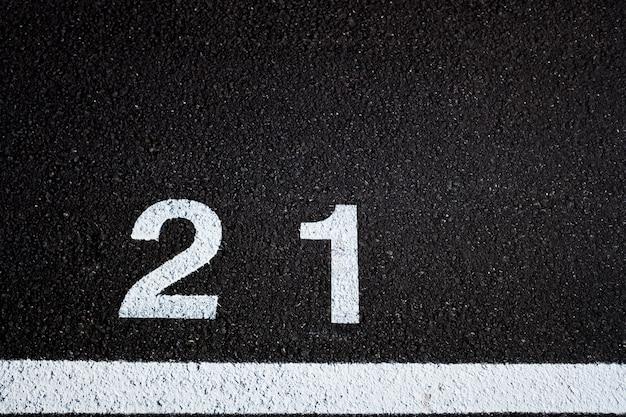 Numéro 21, âge légal, peint sur le sol pavé d'un parking peint en blanc,