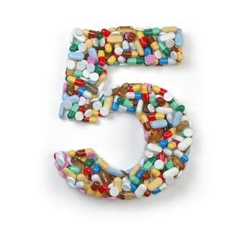 Numéro 5 cinq de comprimés de capsules de pilules de médecine et de boursouflures d'isolement sur le blanc