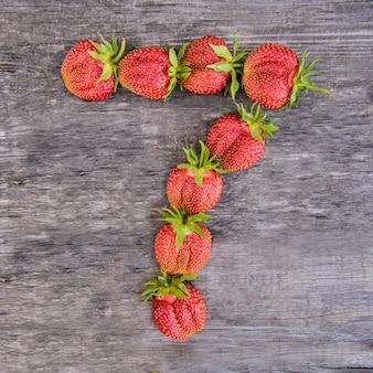 Numéro 7 de fraises sur fond de bois