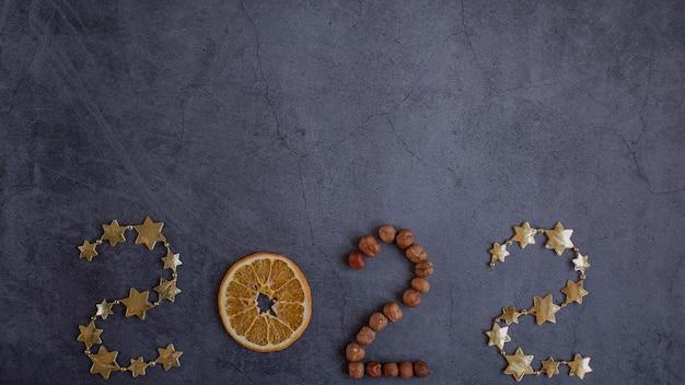 Numéro de bannière 2022 d'étoiles noix et orange sur fond sombre espace d'idées créatives pour le texte