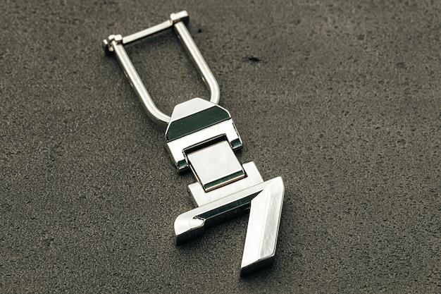 Numéro de métal sept clé de voiture sur fond de béton foncé close up