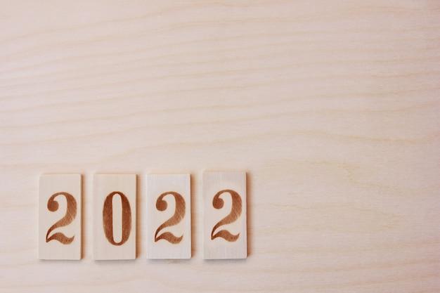 Numéro de nouvel an 2022 bordé de figures en bois sur la surface en bois. bonne année.