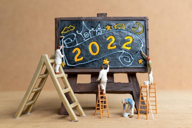 Numéro de peinture de l'équipe de travailleurs miniatures 2022 sur tableau noir, concept de bonne année