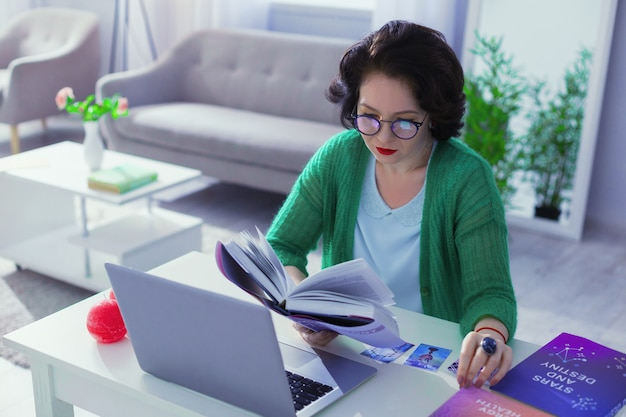 Numérologue professionnel. belle belle femme étudiant la littérature spéciale tout en travaillant comme numérologue
