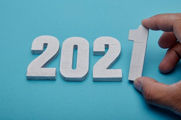 Numéros 2021 et main sur fond bleu pastel pour le nouvel an